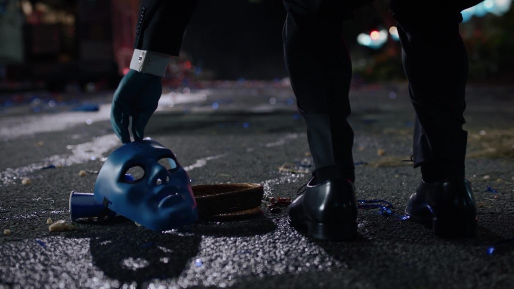 Doctor Manhattan nhặt chiếc mặt nạ trên đường